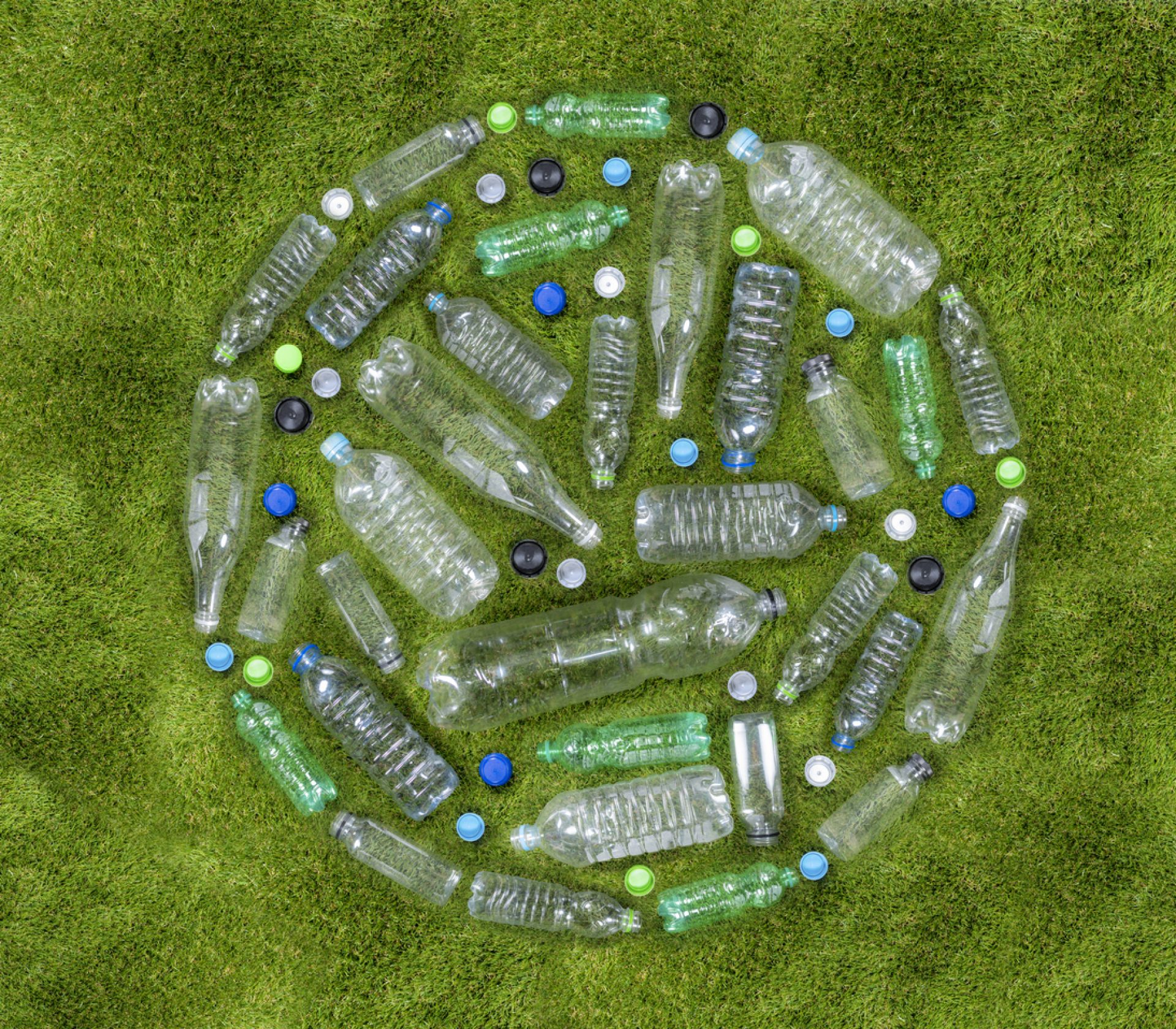 Plastic drinks bottles arranged in a circle on grass